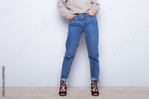 b1f8ffae76 Fashion jeans on a girl. Thin legs of fashion girl. Shapely female legs in  high heel shoes and jeans near a white wall