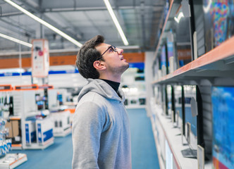 Smart modern male customer examining large TV-sets at electronics store. He looks at new display.. New screen generations.