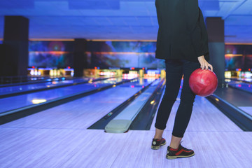 A woman in business wearing a bowling red shark. The legs of a woman playing bowling.
