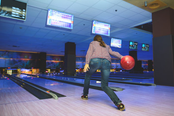 The woman plays bowling. A woman throws a layer on the bowling lane to knock down the skewers. Bowling game.