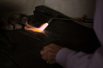 Goldsmith hands using welding torch in workshop