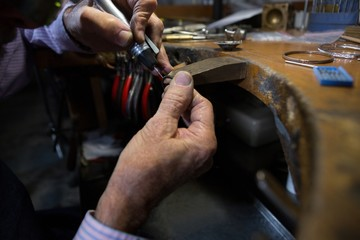 Goldsmith working at desk in workshop