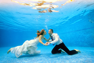 Loving couple in wedding dress swims underwater in the pool to meet each other. Horizontal view. Shooting from under the water