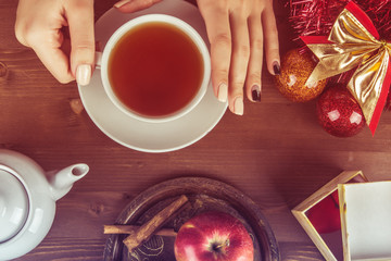 Hands of a girl with a cup of tea on a background of a Christmas composition with toys and fruits