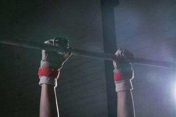 Male gymnast hands practicing gymnastics on the horizontal bar