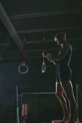 Male gymnast practicing on gymnastic rings