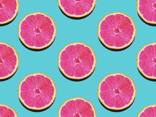 Tuinposter Pop Art Grapefruit in flat lay Fruity pattern of grapefruit with pink flesh on a turquoise background Top view Modern flat lay photo pattern in pop art style