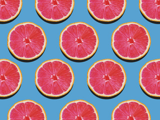 Grapefruit in flat lay Fruity pattern of grapefruit with red flesh on a blue background Top view Modern flat lay photo pattern in pop art style