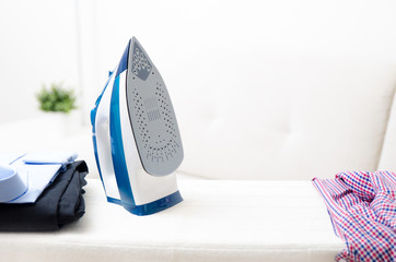 Steam blue iron on ironing board