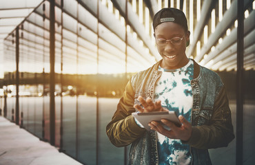 Young black man in jean jacket, cap and glasses is using digital tablet to send a message while standing outside on street near contemporary building facade with copy space zone for logo or your text