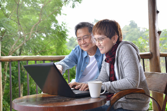 Happy senior couple using laptop computer at home with green garden background