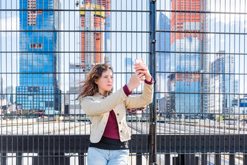 Closeup of young hipster millennial woman taking selfie picture with phone at Hudson Yards in NYC New York City Manhattan downtown on high line park and trains behind fence