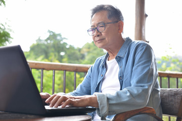 Senior man working on laptop computer at home with green garden  background