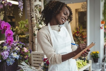 Female florist noting order in dairy while talking on mobile