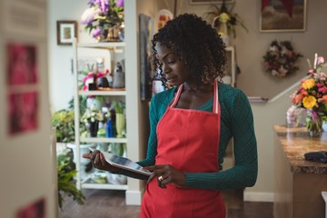 Female florist using digital tablet while standing in shop