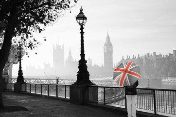 Fotomurales - UK - Cities - Palace of Westminster in fog seen from South Bank, one  Tourist with Union Jack Umbrella Present