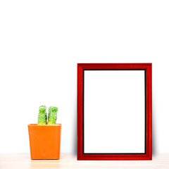 Red frame with cactus in pot on wood table
