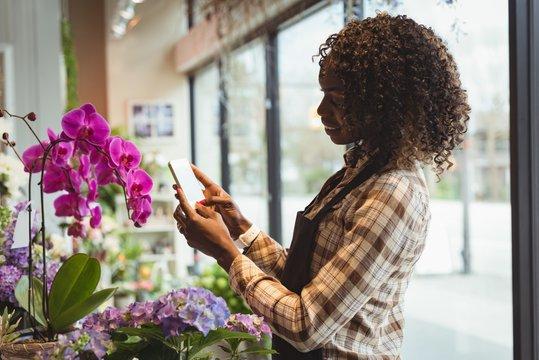 Female florist taking photograph of flower bouquet