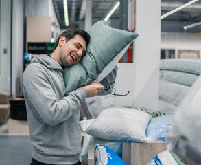 Customer man chooses bed linen and bed in the supermarket mall store. He is relaxing with comfortable pillow.