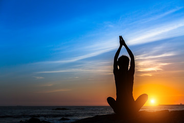 Yoga meditation woman on the ocean during amazing sunset.