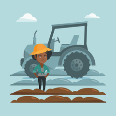 African-american farmer in summer hat standing on the background of tractor preparing land. Young smiling farmer standing in a field in front of tractor. Vector cartoon illustration. Square layout.