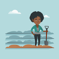 Young african farmer standing with a shovel on the background of plowed field. Farmer working in field with a shovel. Farmer plowing field with a shovel. Vector cartoon illustration. Square layout.