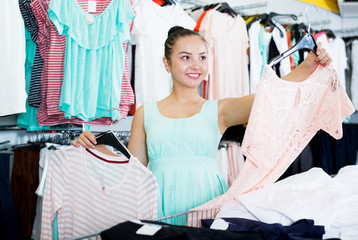 Brunette choosing new clothes in shop