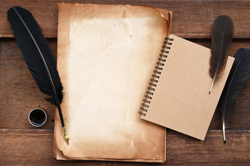 old paper on brown wood texture with feather and ink, blank notebook for background