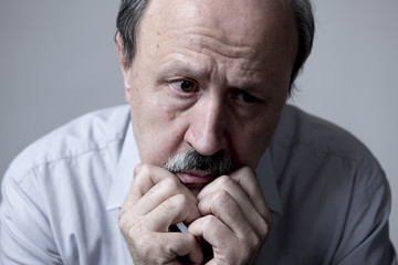 head portrait of senior mature old man on his 60s looking sad and worried suffering pain and depression in sadness face expression