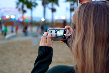 Woman Taking Photo with Smartphone at Dusk on Beach with Palm Trees