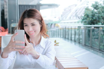 Attractive young Asian woman taking photo or selfie on mobile smart phone in office. Selective focus and shallow depth of field.
