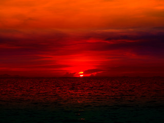 sunset last light of sun on horizontal line over red sky and ocean