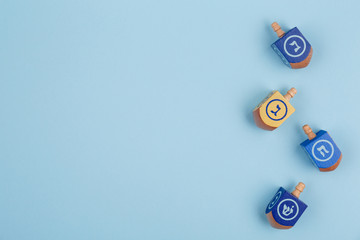 Blue background with multicolor dreidels. Hanukkah and judaic holiday concept.