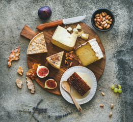 Flat-lay of cheese platter with cheese assortment, figs, honey and nuts over grey concrete background, top view. Party or gathering eating concept