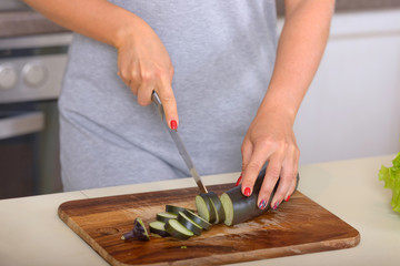 Woman cuts slices eggplant on cutting board