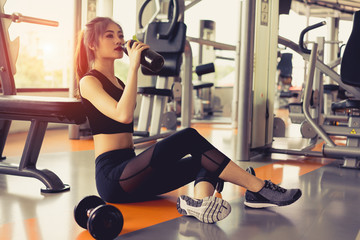 Woman exercise workout in gym fitness breaking relax drinking protein shake bottle after training sport with dumbbell and healthy lifestyle bodybuilding.