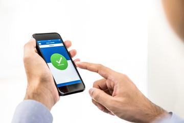 Businessman using smartphone application transferring money online