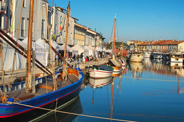 CESENATICO, ITALY: 01 JANUARY 2017- Christmas Fair kiosks on the embankment of the port channel with the typical fishing boats of the Adriatic Sea