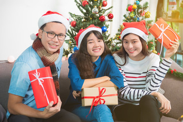 Young adult asian people sitting on sofa and smile in christmas party