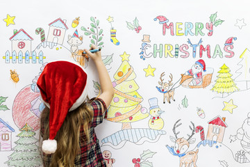 Little girl drawing Christmas pictures on a white wall