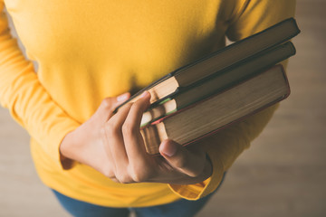 Hands of female student in yellow sweater carrying books in a library