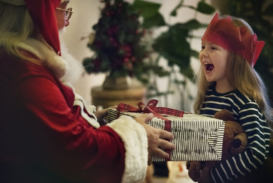 Santa Claus giving out a gift to a little girl