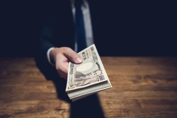 Businessman giving money, Japanese Yen banknotes, over his desk in dark office