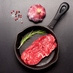 Wall Mural - Raw steak Ribeye entrecote with rosemary in a cast-iron frying pan