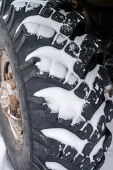 Snow-covered big truck wheel with deep tread.