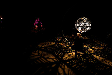 """A visitor poses for a photo in the installation """"Celestial Shadows"""" which is part of the exhibit """"Enchanted: Forest of Light"""" at Descanso Gardens in La Canada Flintridge"""