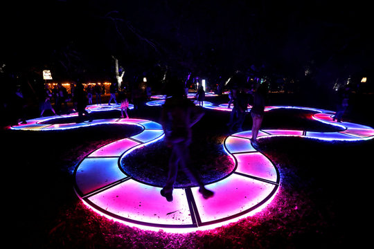 """Visitors interact with the installation """"Luminous Lawn"""" which is part of the exhibit """"Enchanted: Forest of Light"""" at Descanso Gardens in La Canada Flintridge"""