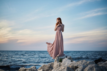 Young beautiful woman in a long pink dress is standing on stones on the seashore