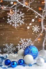 Christmas decorative balls on snow and Christmas lights.