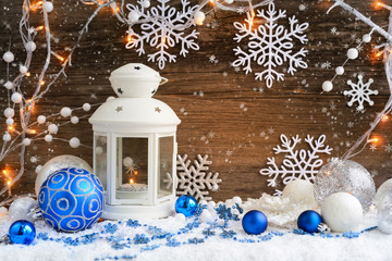 Christmas composition with lantern and Christmas lights on wooden background